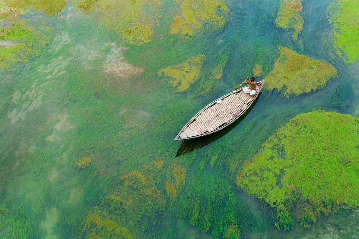 « Pendant l'hiver, un homme à bord d'une barque traverse la rivière Baral lorsque celle-ci se ...