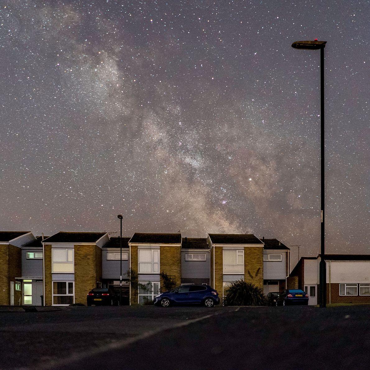 Les lampadaires éteints mettent en lumière un panorama étoilé spectaculaire au-dessus du village côtier de Pagham, ...