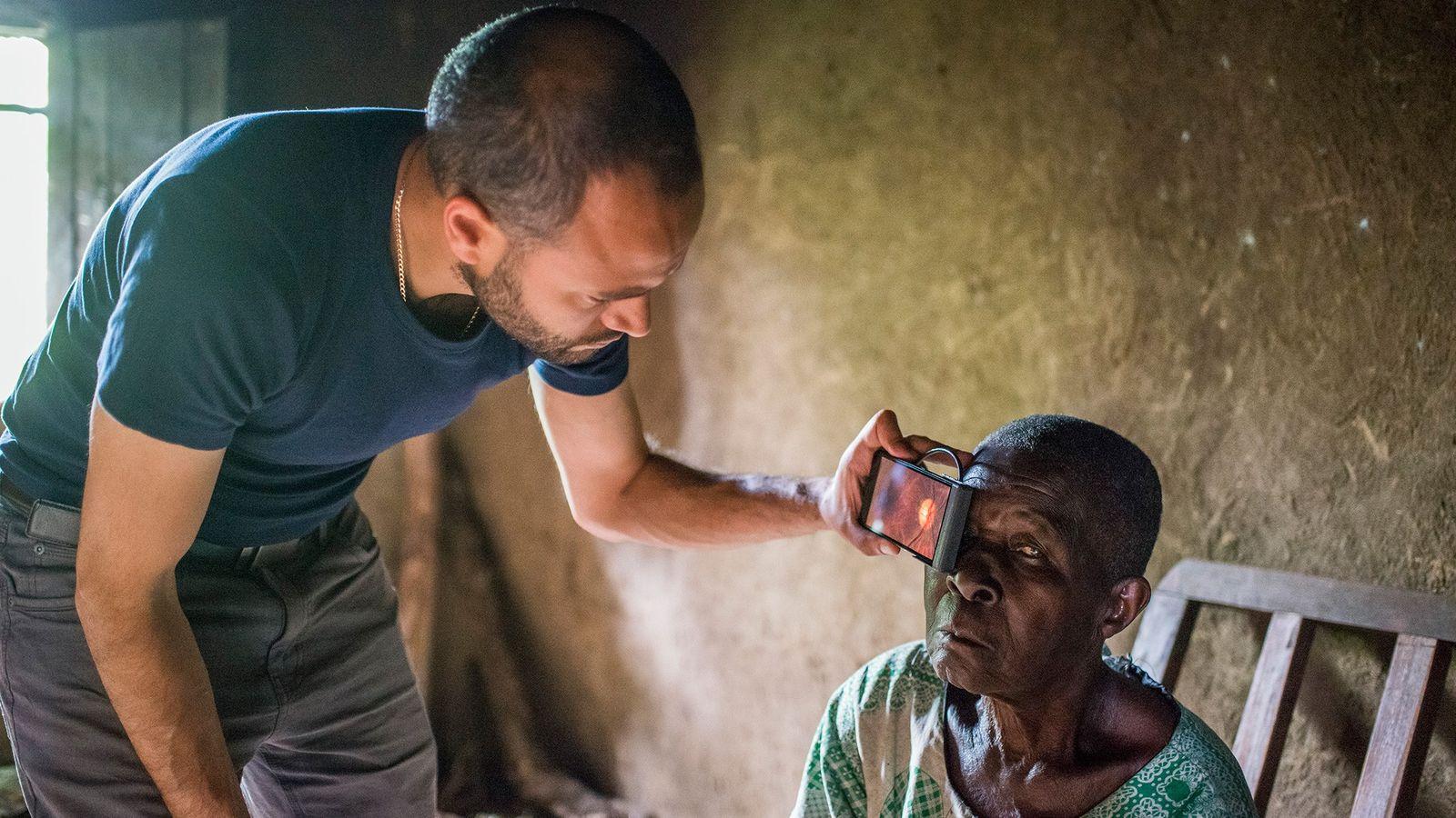 À l'aide de son smartphone, Andrew Bastawrous examine une femme qui souffre de la cataracte.