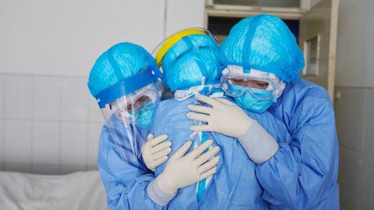 Accolade entre membres du personnel médical au sein d'une unité d'isolement d'un hôpital de Zouping, dans ...