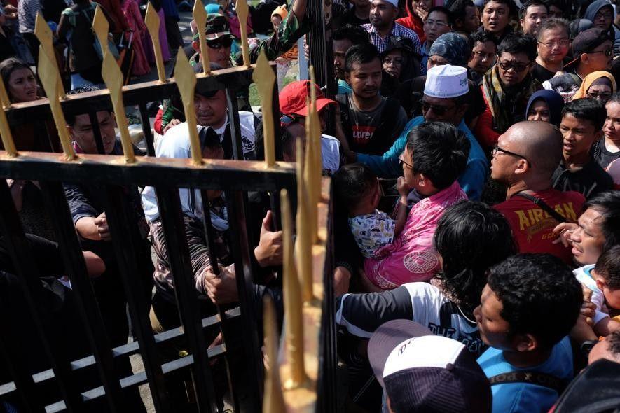 Sur cette photo prise le 30 septembre 2018, des habitants essayent de franchir une grille pour ...