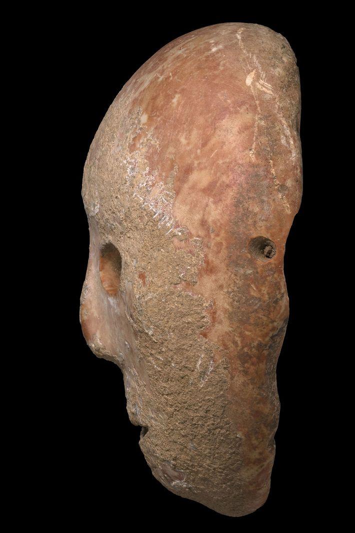 Des trous percés tout autour du masque ont conduit certains chercheurs à penser qu'il était peut-être ...
