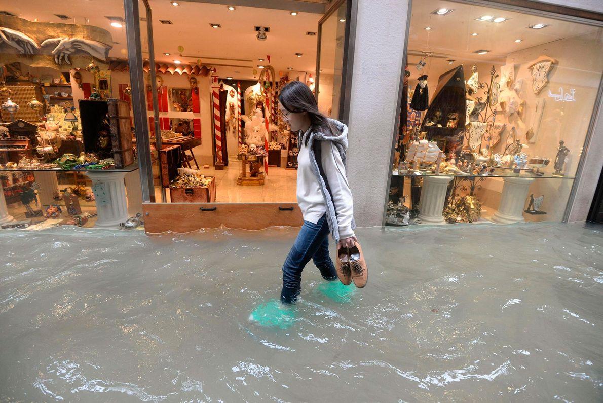 Une femme marche dans une rue vénitienne inondée. Selon la municipalité, environ 75 % de la ...