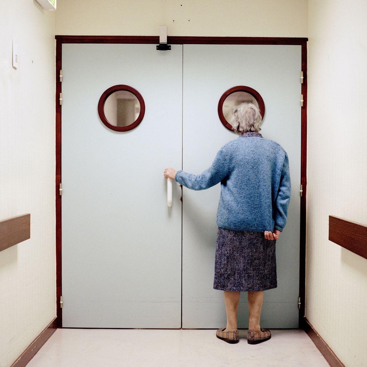 Une résidente se tient devant la porte verrouillée menant à la sortie du département.