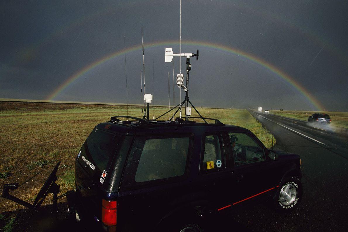 Des chasseurs de tornades étudient un ciel sombre où un arc-en-ciel parfait est visible. Pour les ...