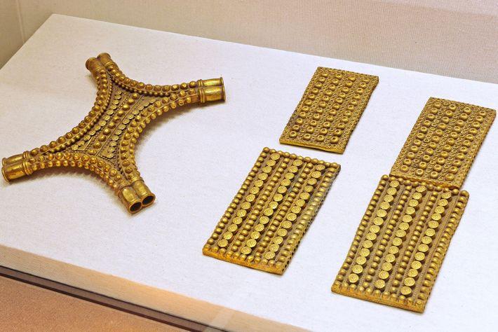 Le trésor comprend des plaques d'or en forme de rectangles et de peaux de bœuf, et ...