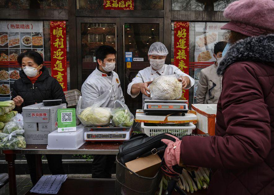 À Pékin, des vendeurs de fruits et légumes portent un masque de protection. Selon une étude ...