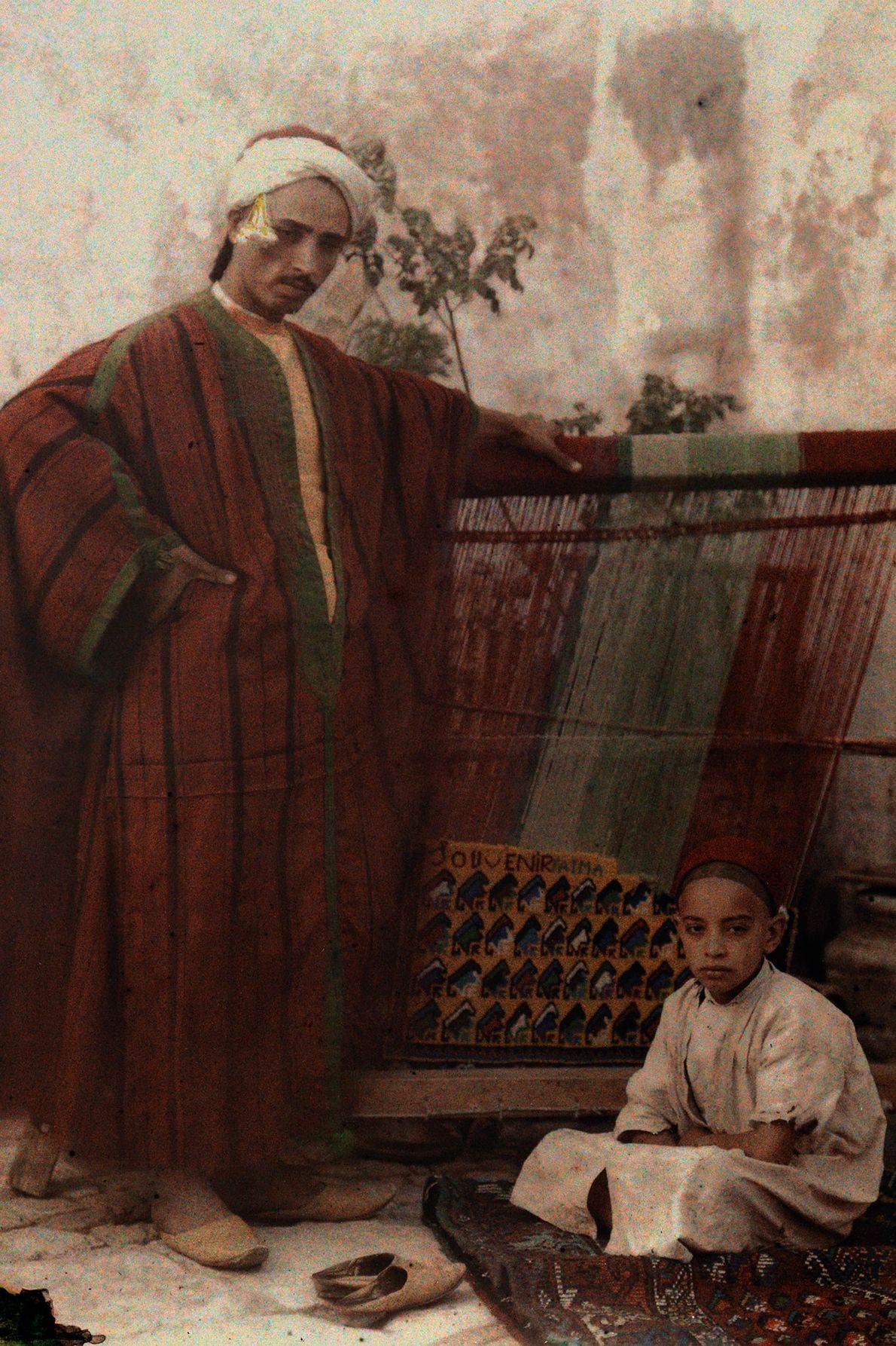Un père et son fils prennent la pose devant un métier à tisser en Tunisie au ...