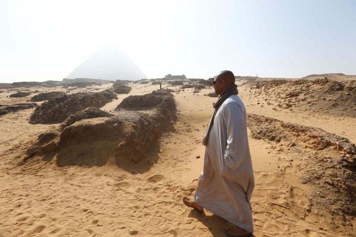 Un homme marche près du tombeau récemment découvert sur le plateau de Gizeh, situé sur la ...