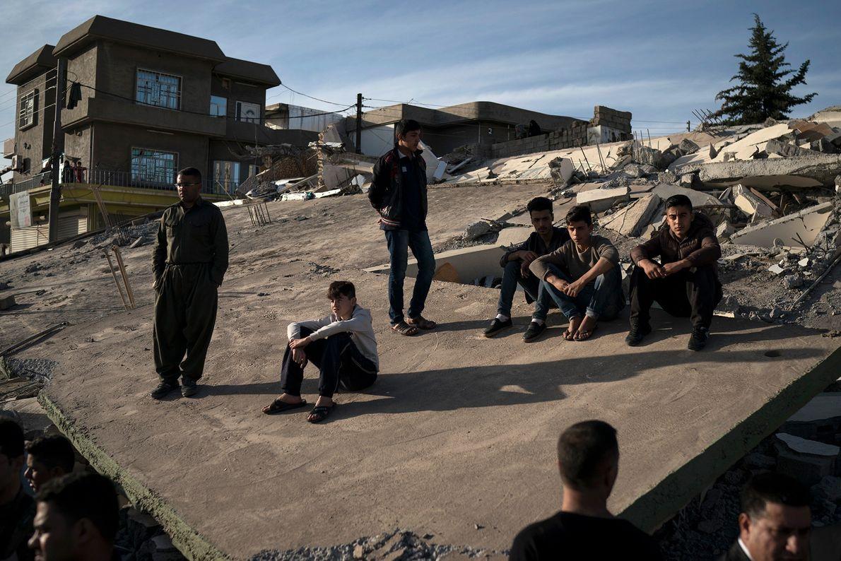Des habitants assis sur le toit des maisons détruites par le séisme dans la ville de ...