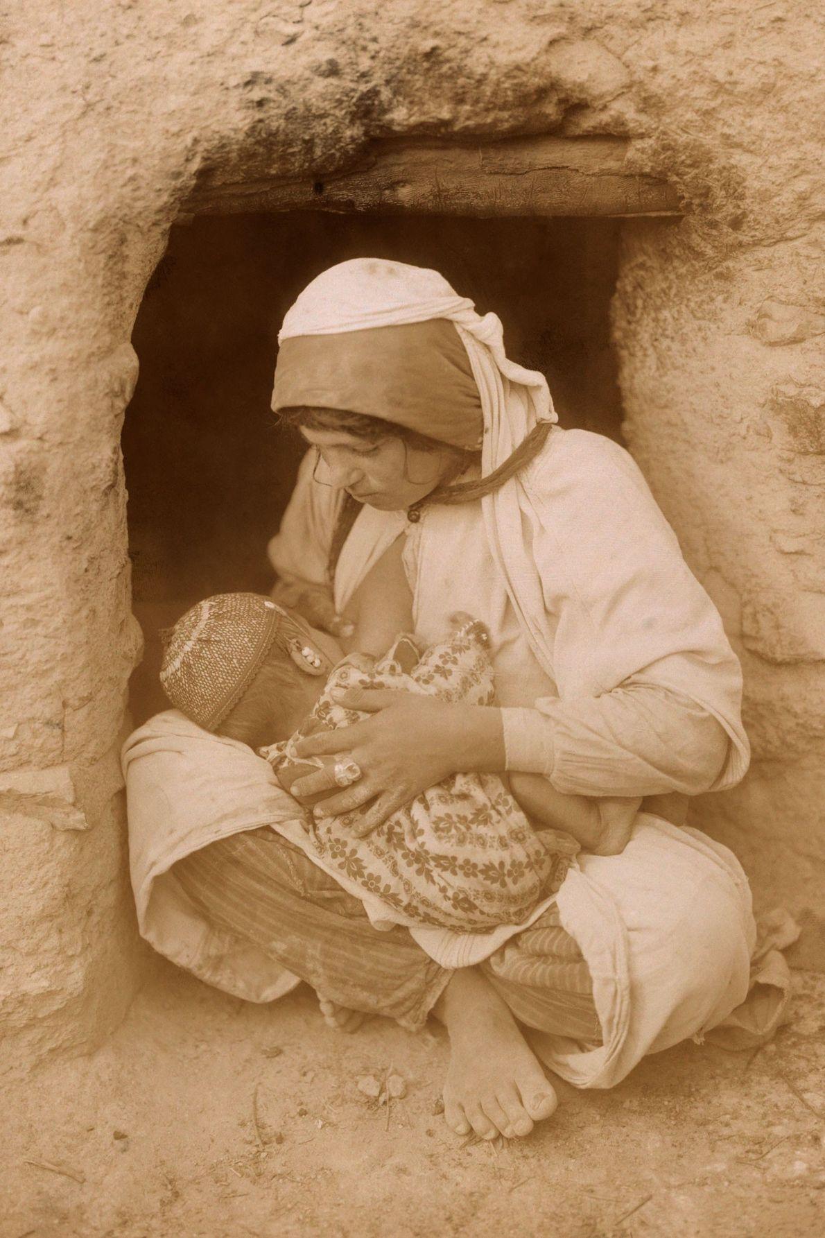 Une mère au Moyen-Orient allaite son bébé devant sa maison.