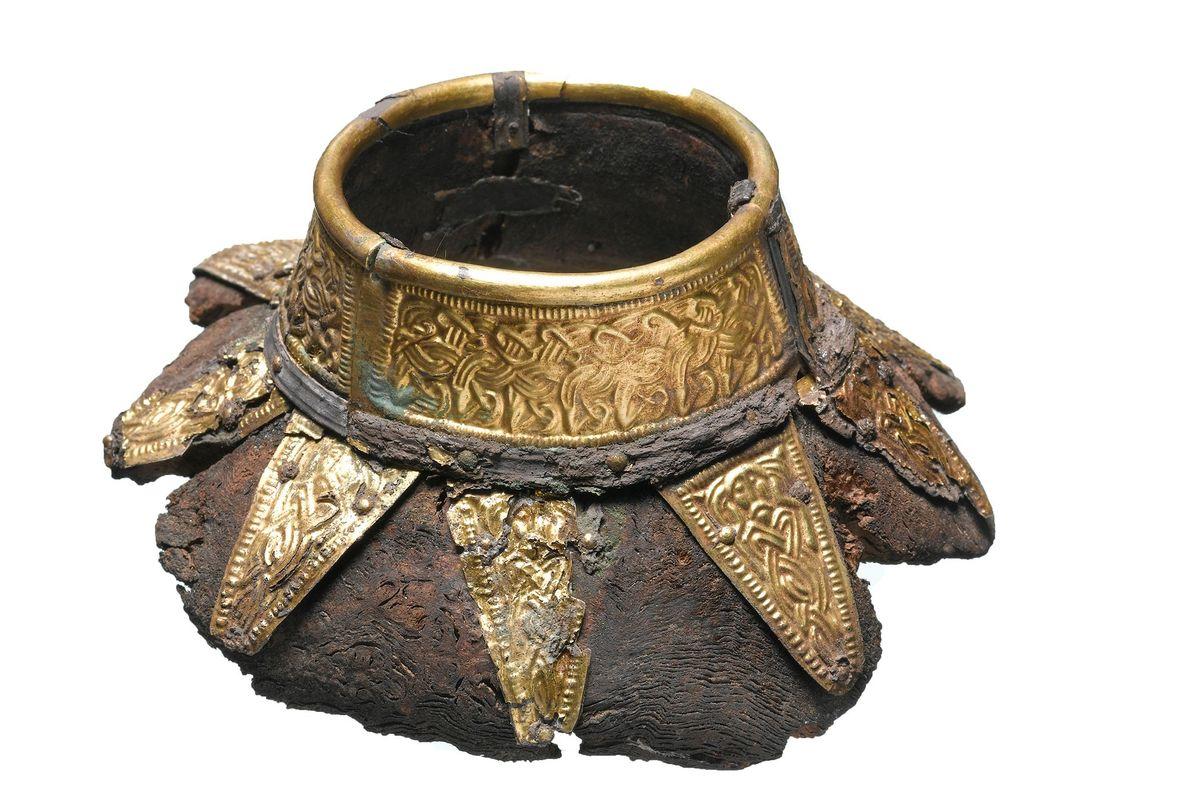 Le haut d'une gourde en bois est décoré de motifs en or.