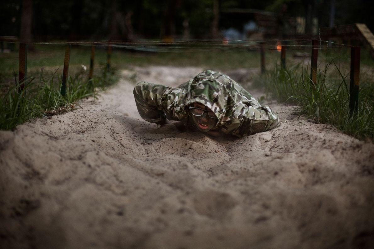 Mathew, 11 ans, rampe sous des fils barbelés pendant des manœuvres militaires au camp LIDER. « ...