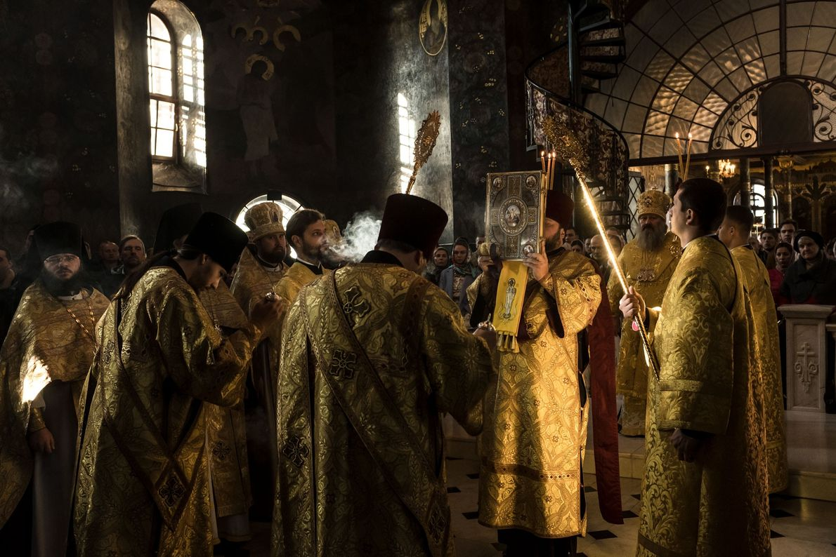 Séparés de leurs fidèles par une balustrade, des prêtes en habits sacerdotaux scintillants s'apprêtent à lire ...