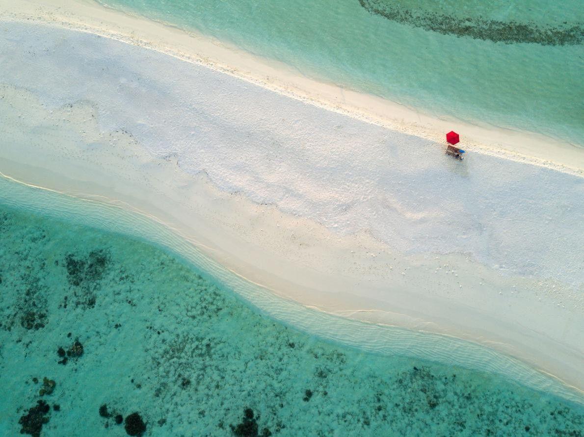 « Un parasol rouge solitaire sur le banc de sable d'un petit îlot dans l'atoll d'Ari ...