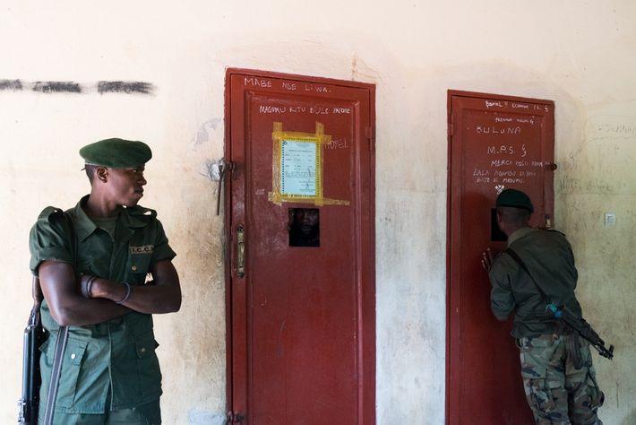 À Epulu, des gardes surveillent deux hommes. Ces derniers ont été arrêtés pour avoir extrait huit ...