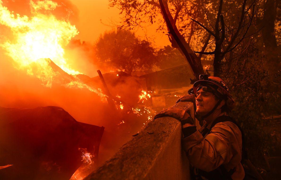 Rick Mullen, maire de Malibu et pompier, surveille une maison en feu victime de l'incendie Woolsey.