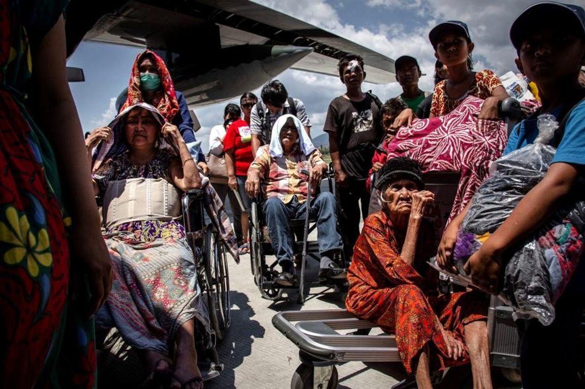 Des personnes âgées patientent avant de monter dans un avion à l'aéroport de Palu, qui a ...