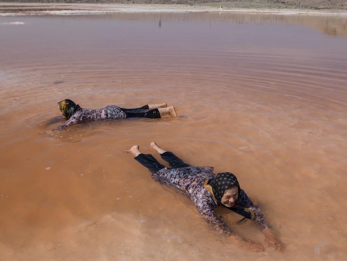 Deux femmes se baignent dans les eaux rouges du lac d'Ourmia, ou du moins, dans ce ...