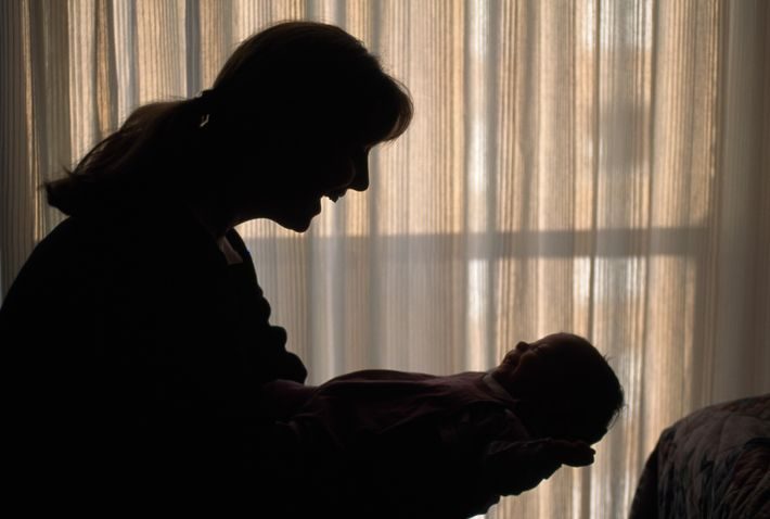 Une maman prend son bébé dans ses bras.
