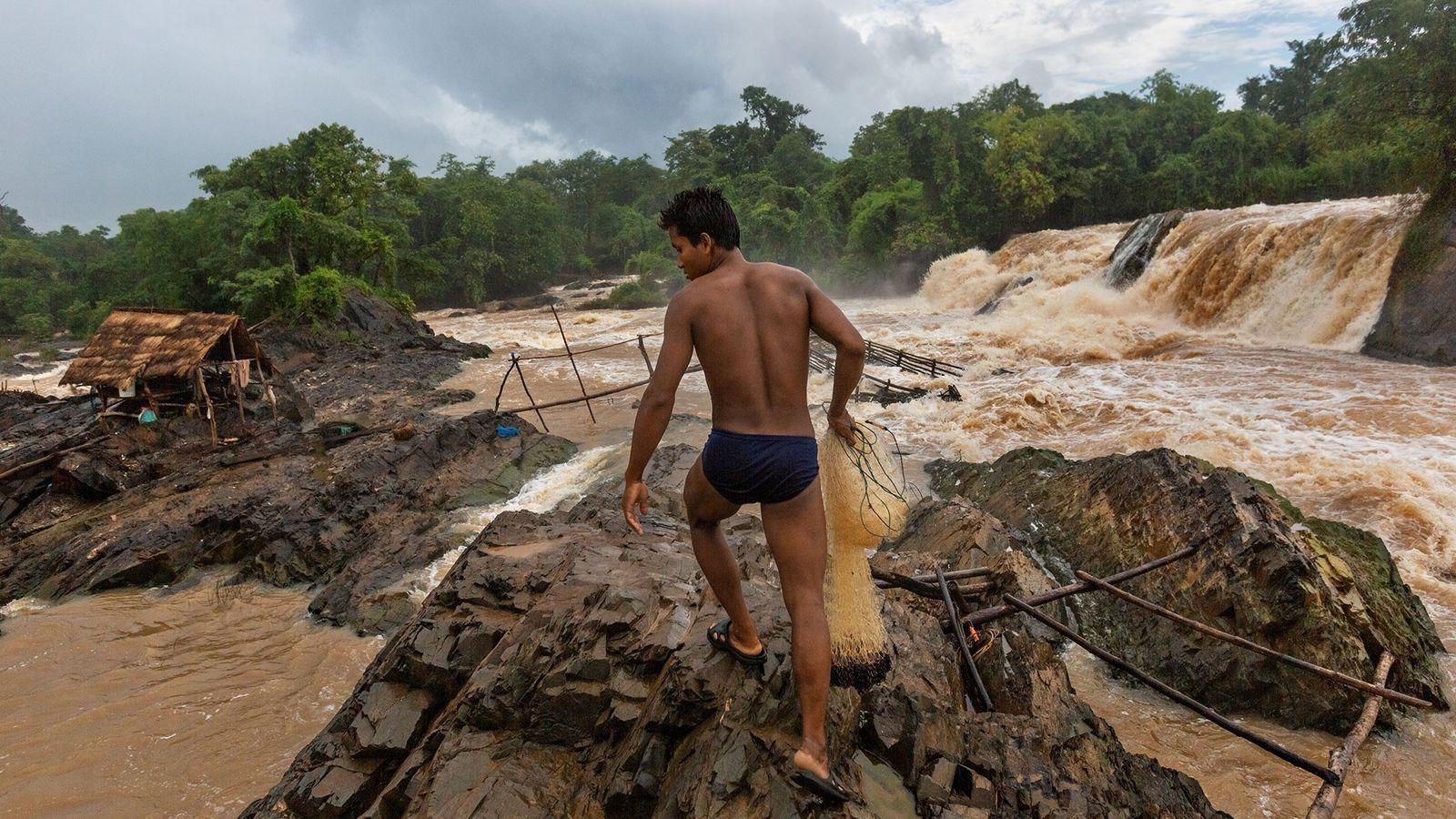 Un pêcheur se prépare à jeter son filet dans une portion des Chutes de Khone, situées ...