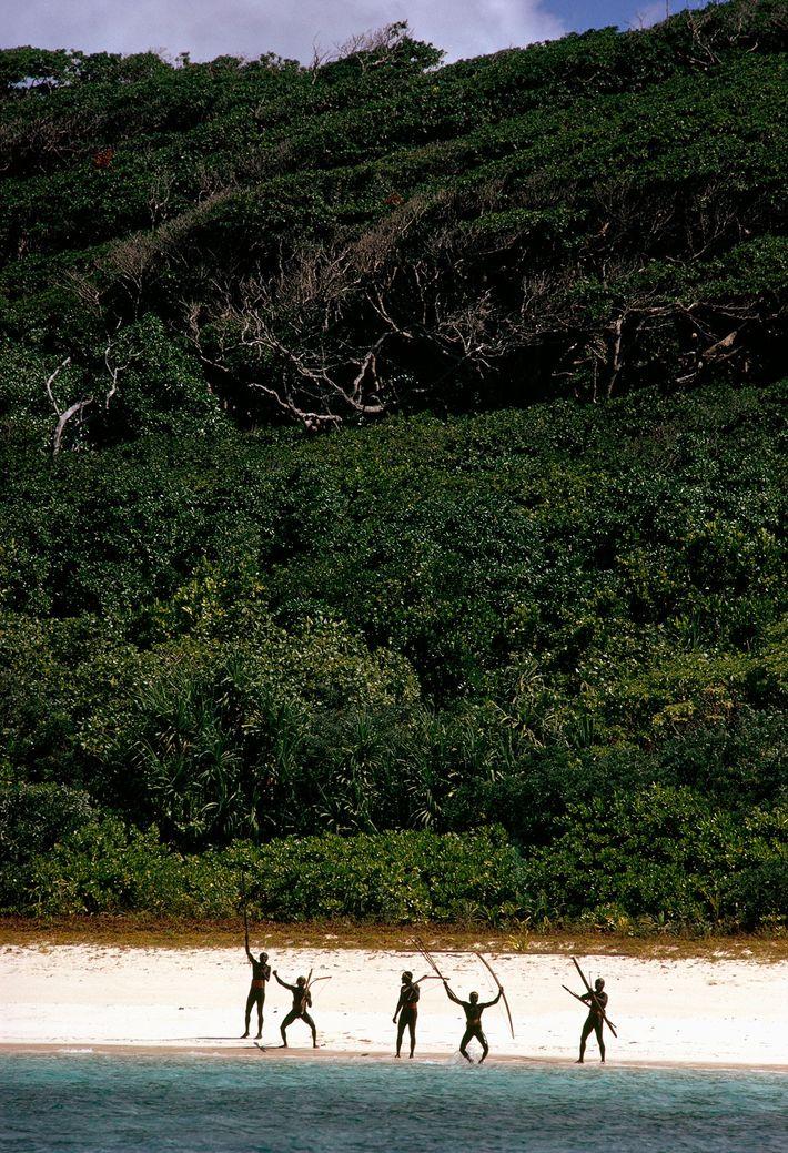 Gesticulant armés de leurs arcs et de leurs flèches le long des plages de l'île, des ...