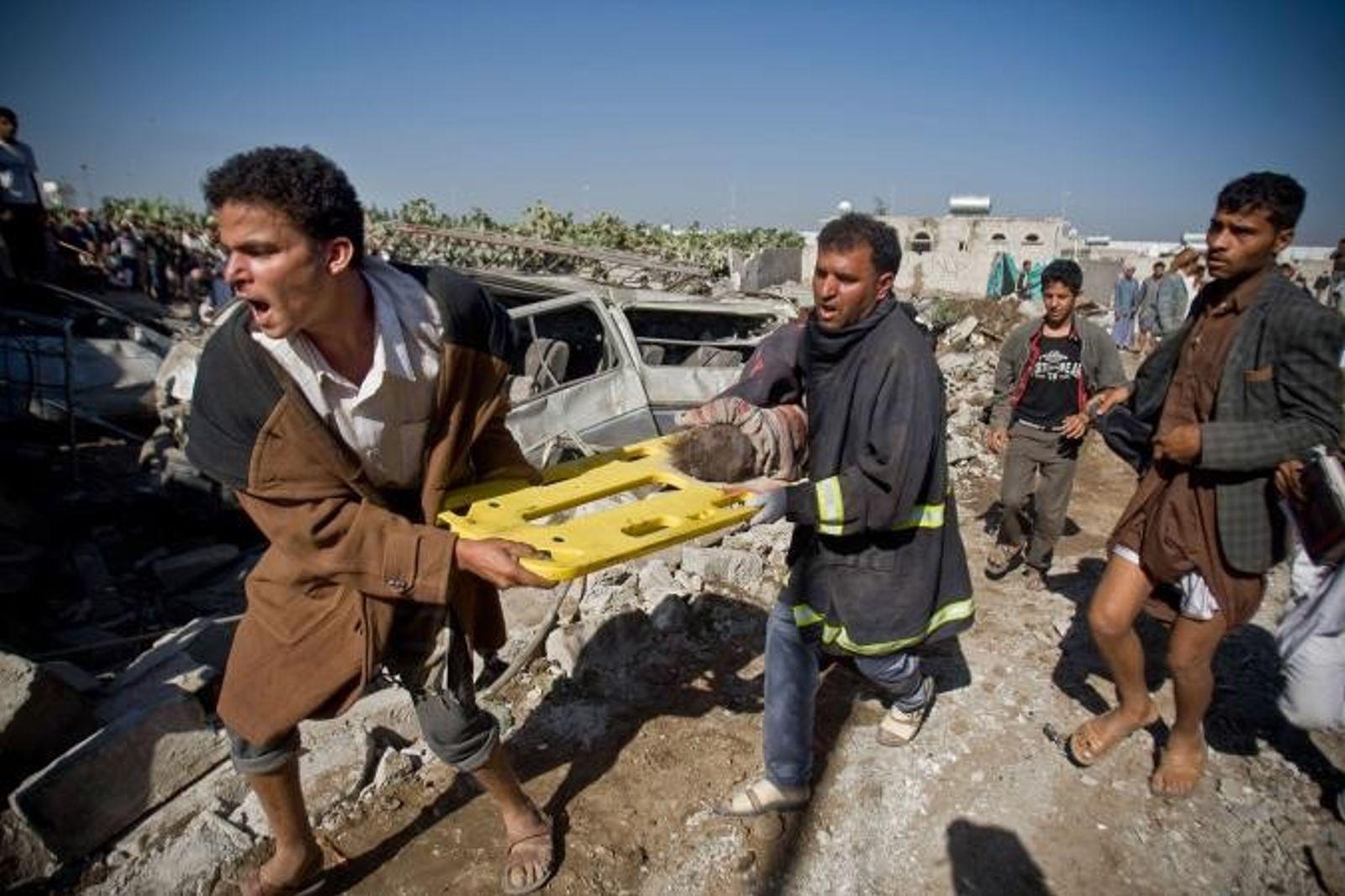 À Sanaa, des personnes transportent le corps d'un enfant qu'il viennent de retrouver sur les décombres ...