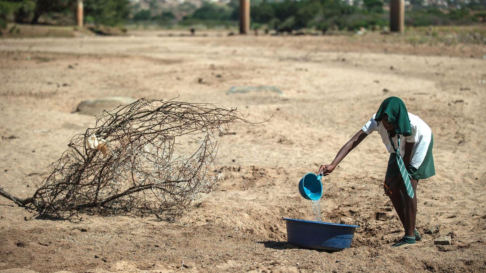 Une écolière tente de collecter de l'eau dans une flaque au nord-ouest de Durban, gravement affecté ...