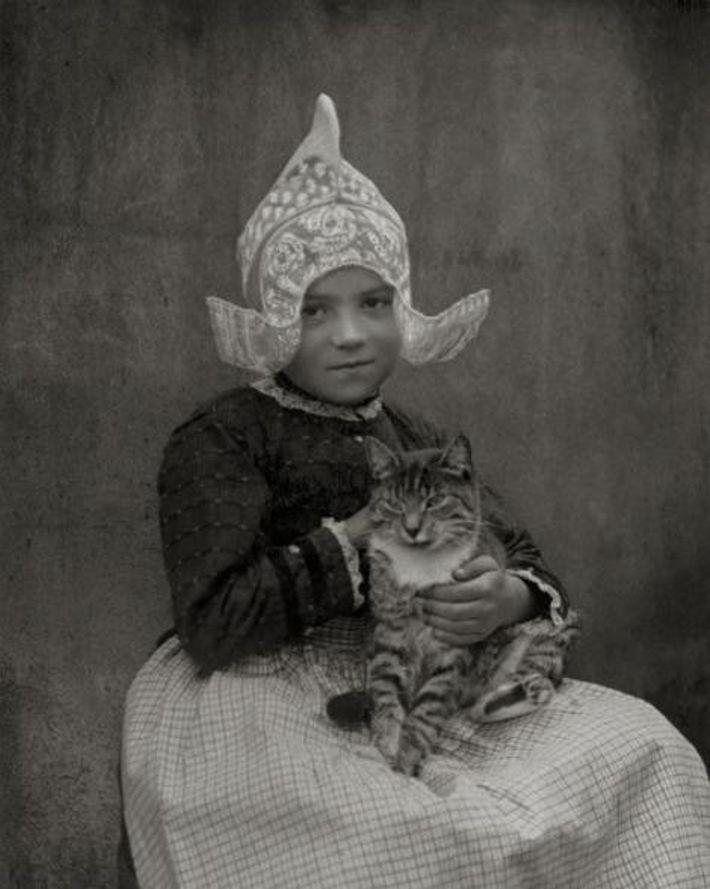 Sur cette photo prise en 1920 à Volendam aux Pays-Bas, une jeune fille caresse un chat ...