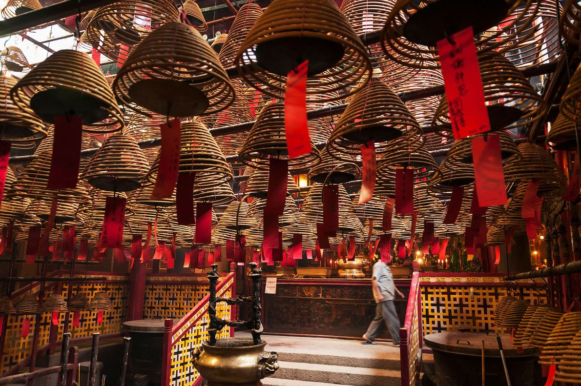 Les vœux des visiteurs inscrits sur du papier rouge pendent aux cônes d'encens accrochés au plafond ...
