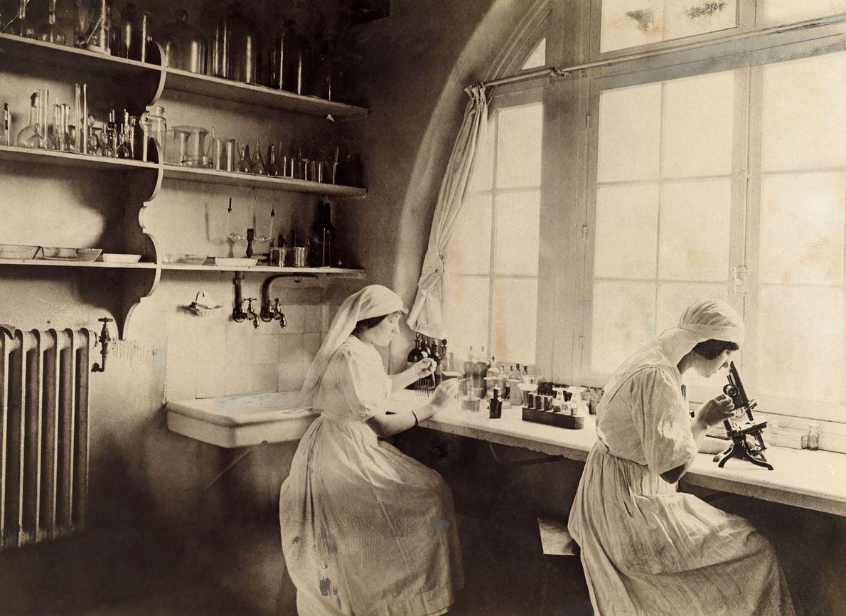 Des infirmières de la Croix Rouge utilisent des microscopes dans un laboratoire de biologie pendant la ...
