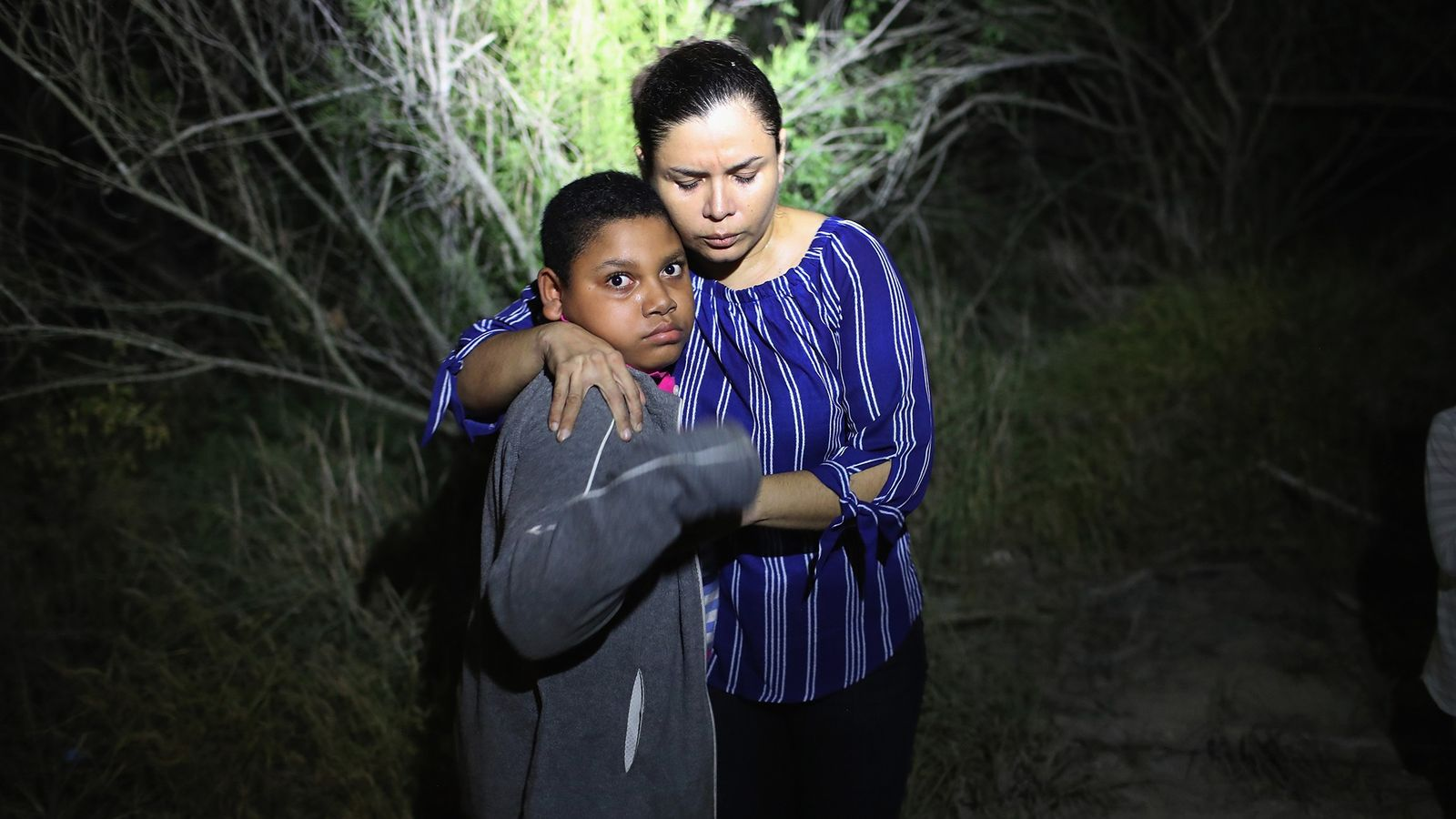 Une mère hondurienne et son fils sont éblouis par le projecteur de la police des frontières ...