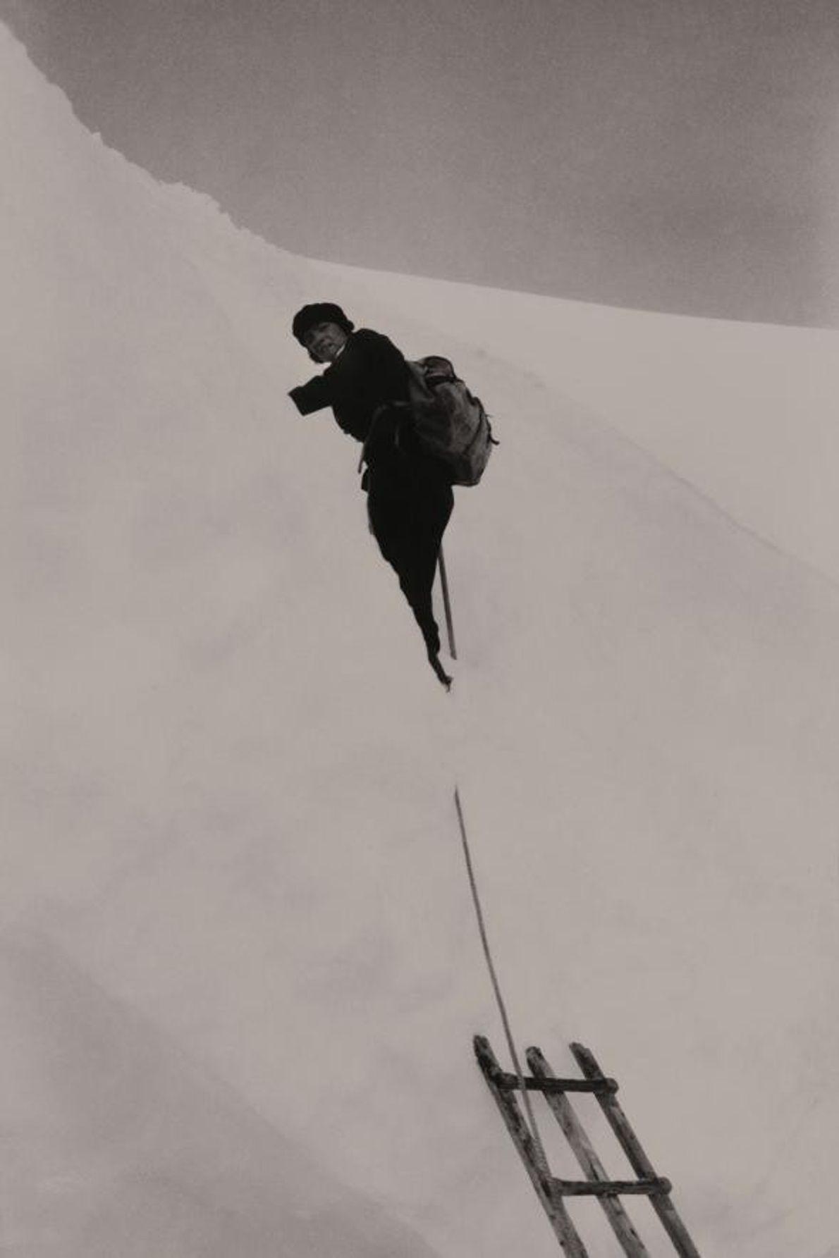 Une alpiniste s'aide d'une échelle pour traverser une crevasse gelée à Jungfrau dans les Alpes bernoises.