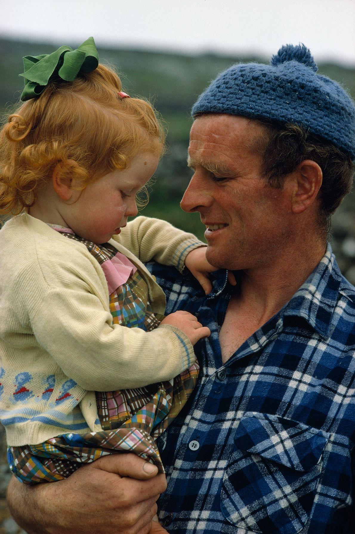 Un pêcheur tient tendrement sa fille dans ses bras sur l'île Inis Meáin, l'une des îles ...