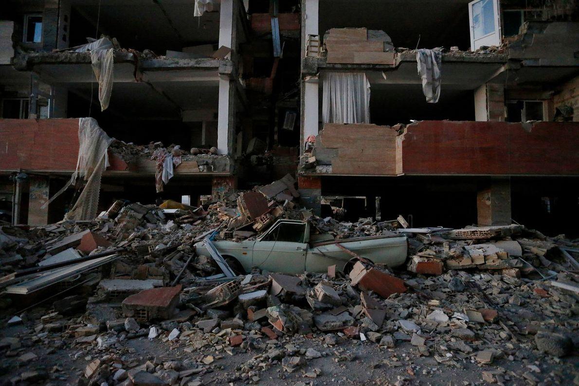 Une voiture écrasée sous les décombres d'un bâtiment après le tremblement de terre de 7.3 de ...