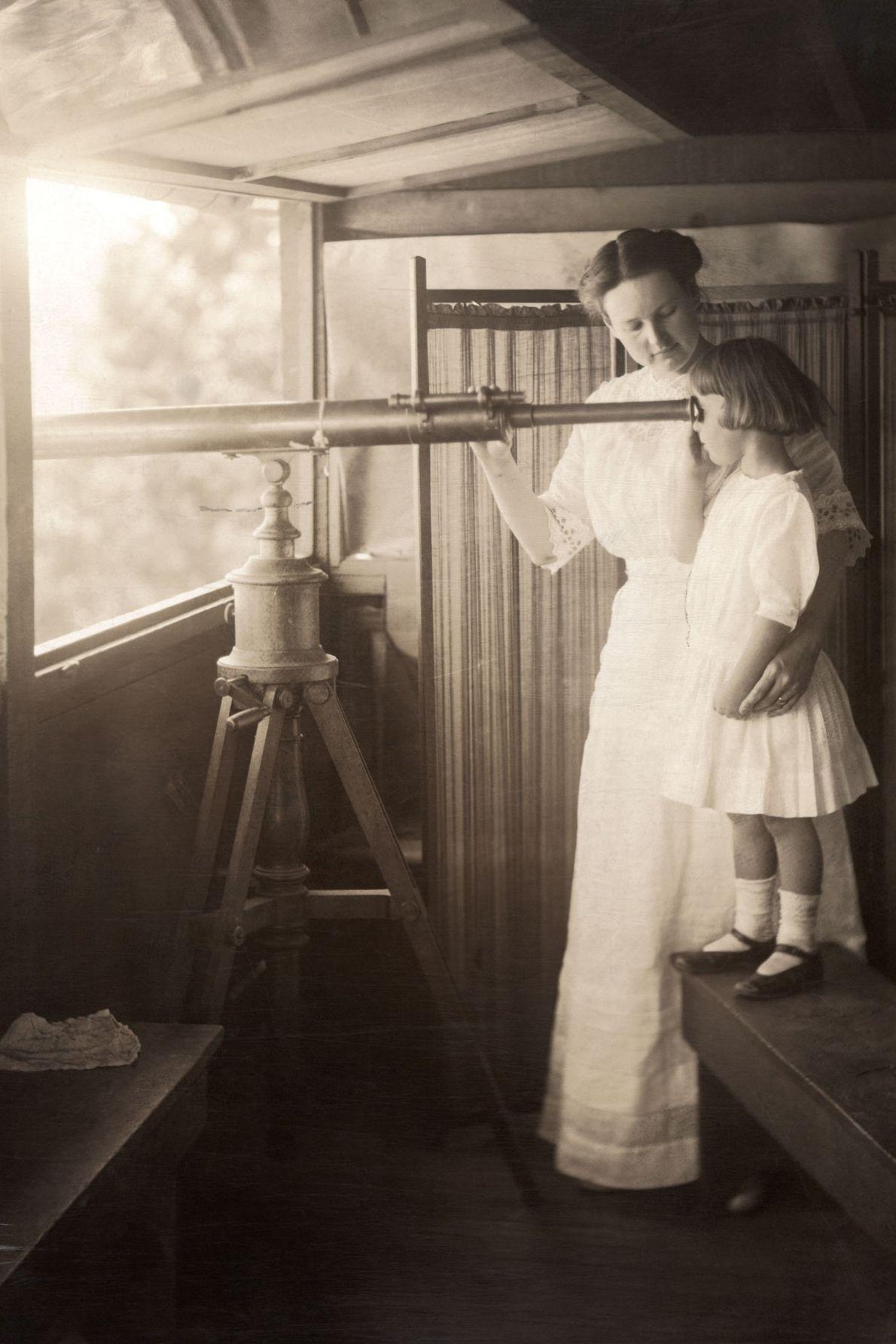 Une mère initie sa fille à voir le monde à travers un télescope dans le Grand ...