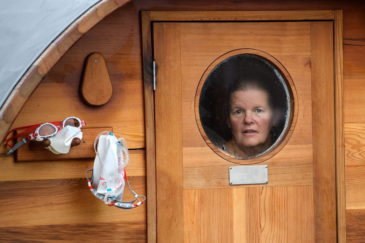 Après sa séance de natation, une femme regarde par le hublot du sauna du Brockwell Lido, ...