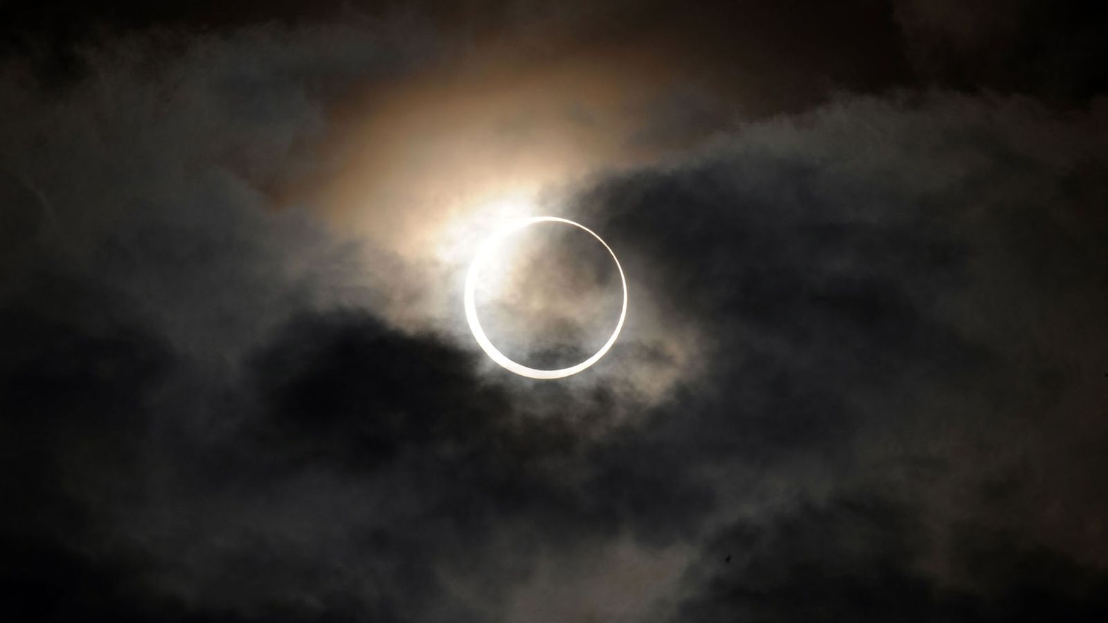 Une éclipse solaire annulaire brille derrière les nuages qui surplombent Tokyo en mai 2012. Les habitants ...