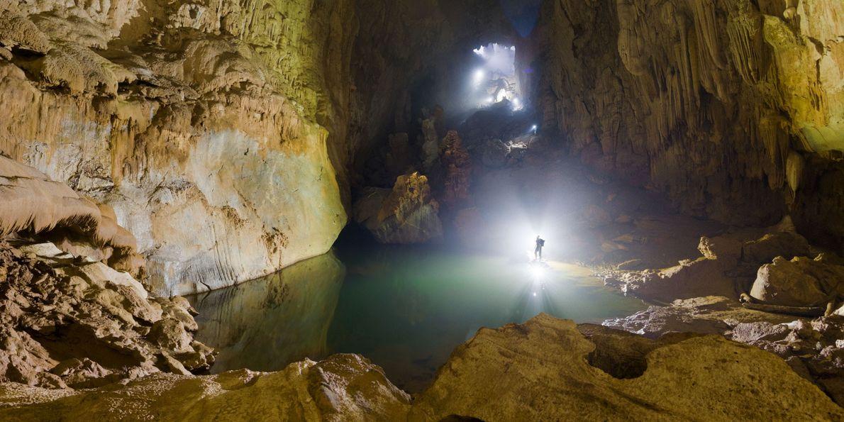 À l'aide de sa lampe frontale, un spéléologue illumine un lac vert à l'intérieur de Son ...