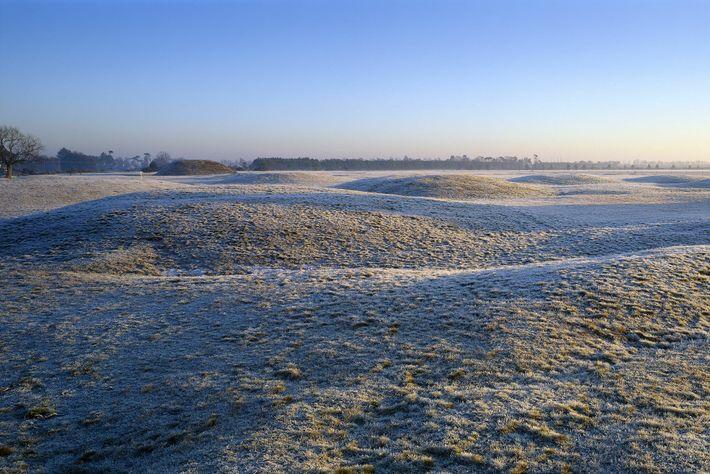 Photographie des tertres funéraires recouverts de givre au petit matin, à Sutton Hoo. Une partie du site ...