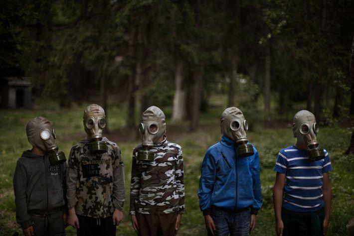 Des jeunes garçons ukrainiens apprennent comment enfiler un masque à gaz en suivant les instructions d'Oleksiv ...