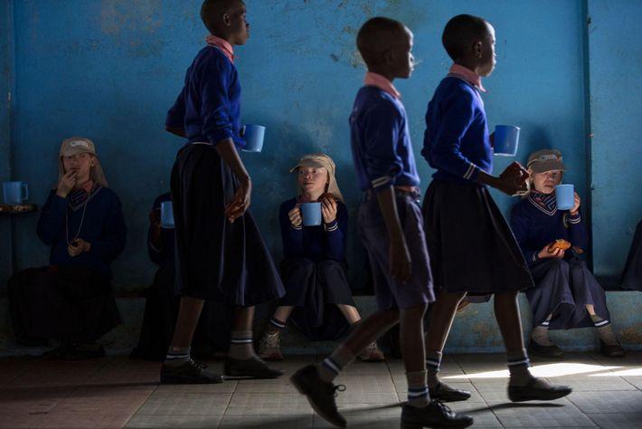 Ces élèves atteints d'albinisme portent des chapeaux et restent à l'ombre pour le thé du matin ...