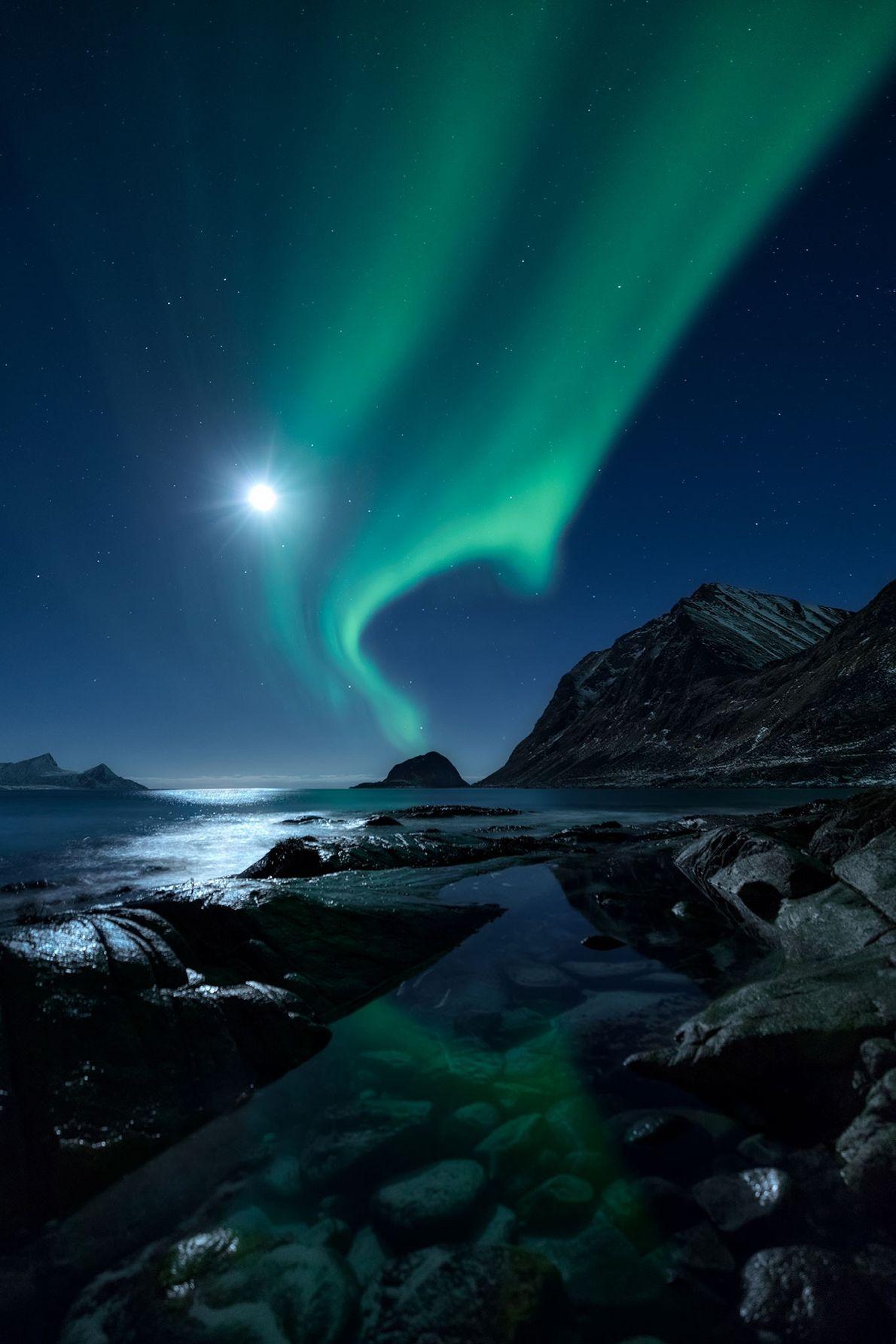 Loin d'être éclipsée par une Lune éclatante, cette aurore boréale flamboie au-dessus d'un fjord au nord ...