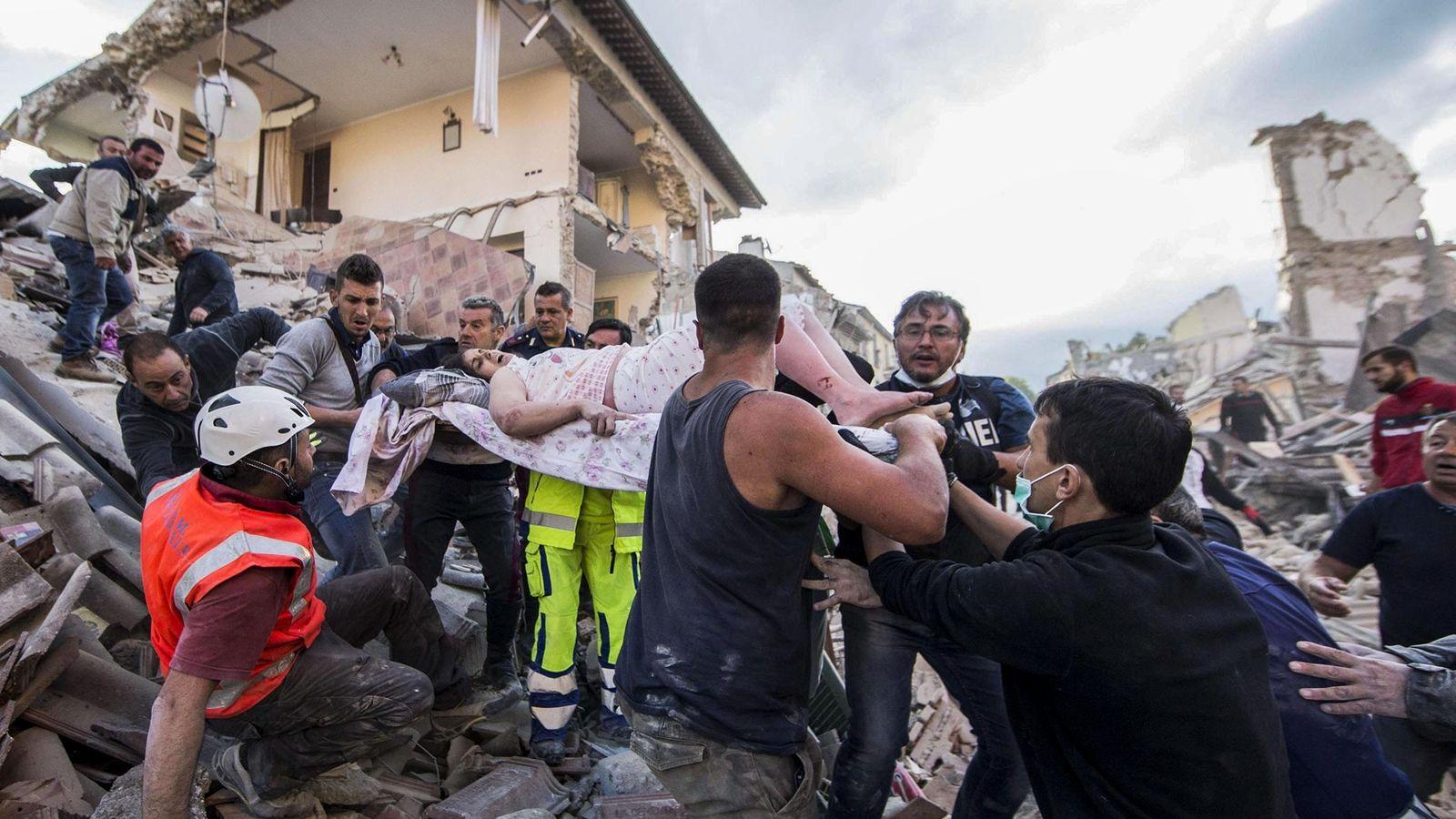 Des secouristes extirpent une femme blessée des ruines d'un immeuble à Amatrice, dans le centre de ...