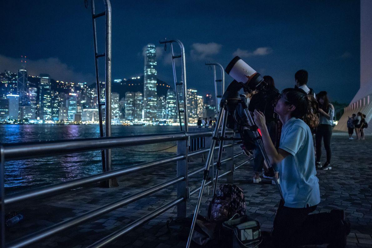 Des gens ont installé des télescopes pour observer l'éclipse lunaire à Tsim Sha Tsui, Hong Kong. ...