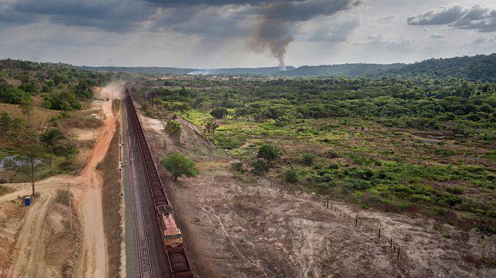 Des trains longs de plus d'un kilomètre, chargés à ras-bord de minerai de fer, passent devant ...