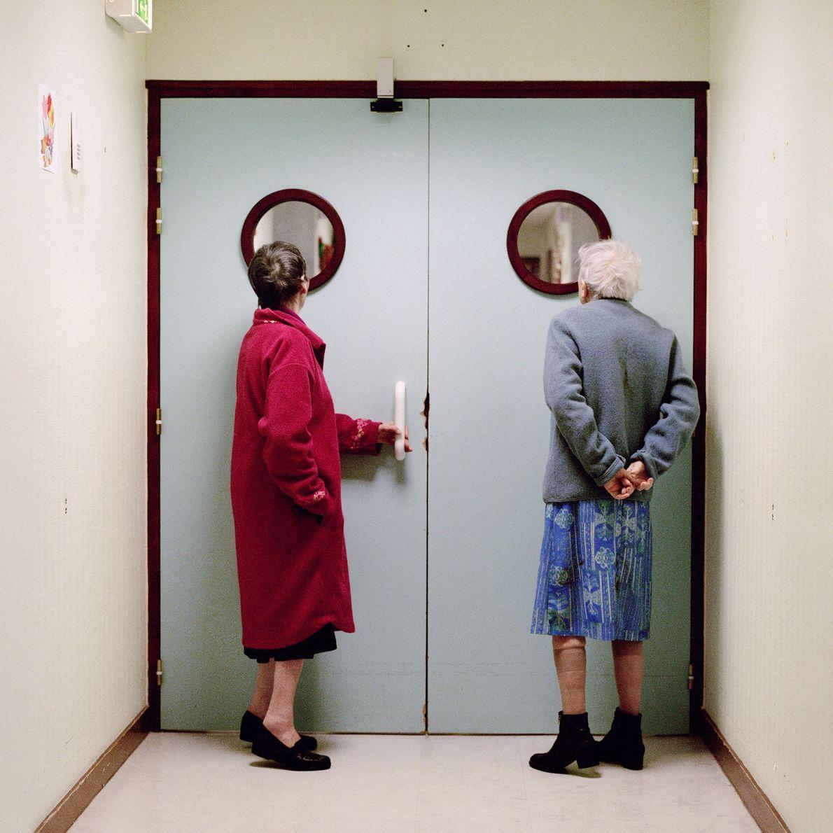 Des résidents jettent un œil à travers le hublot de la porte qui mène vers la ...