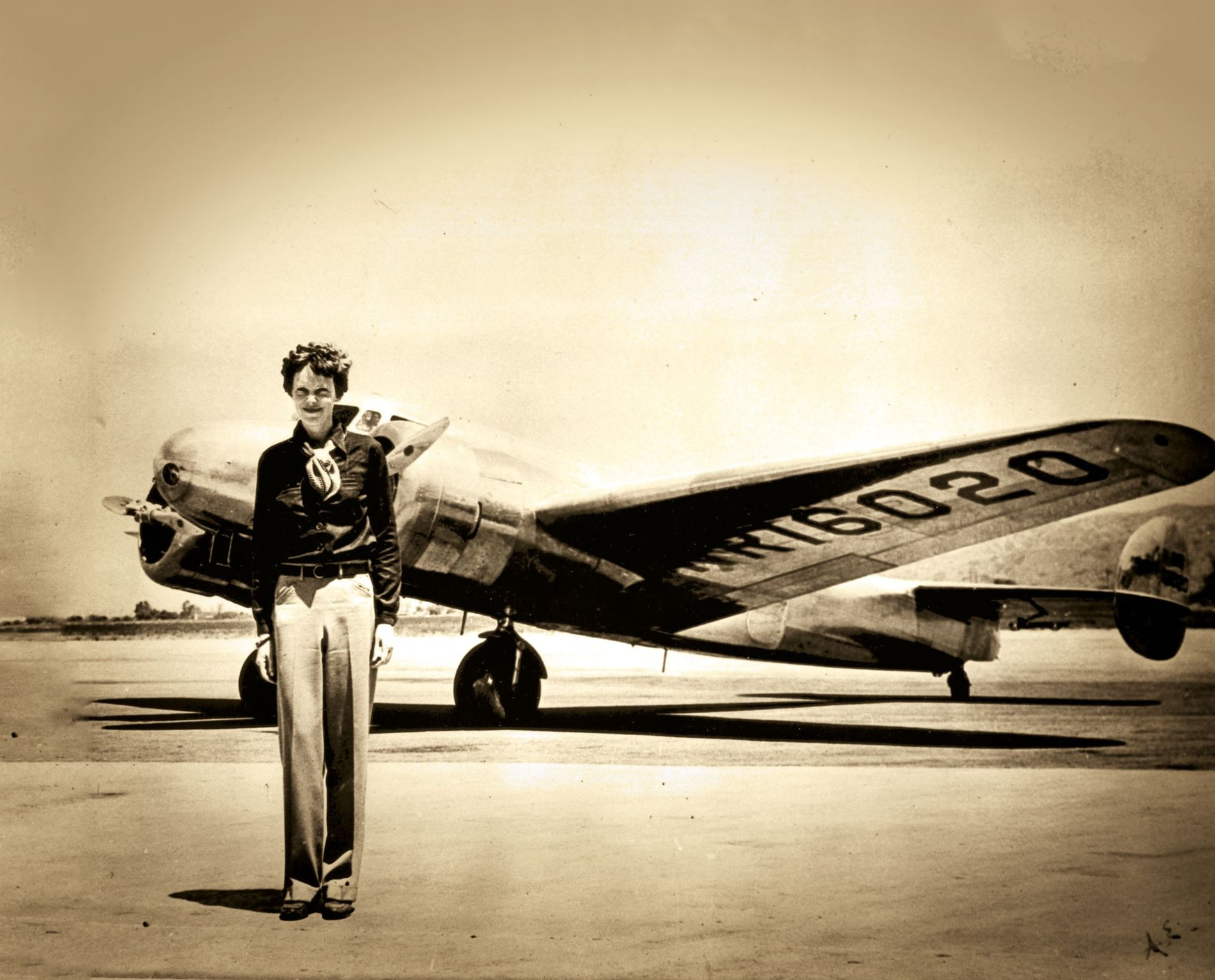Amelia Earhart prend la pose devant son avion, le Lockheed Electra, à bord duquel elle a disparu en juillet 1937.