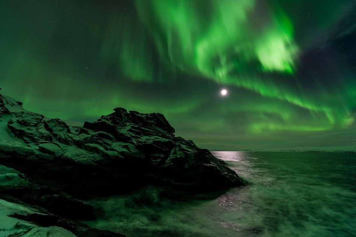 La lune brille pendant une aurore boréale, à Laksefjorden, en Norvège.