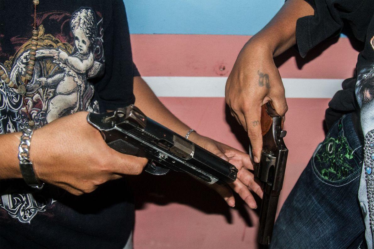 Deux membres de gangs échangent leurs armes avant de partir en patrouille. Quand ils patrouillent, ils ...